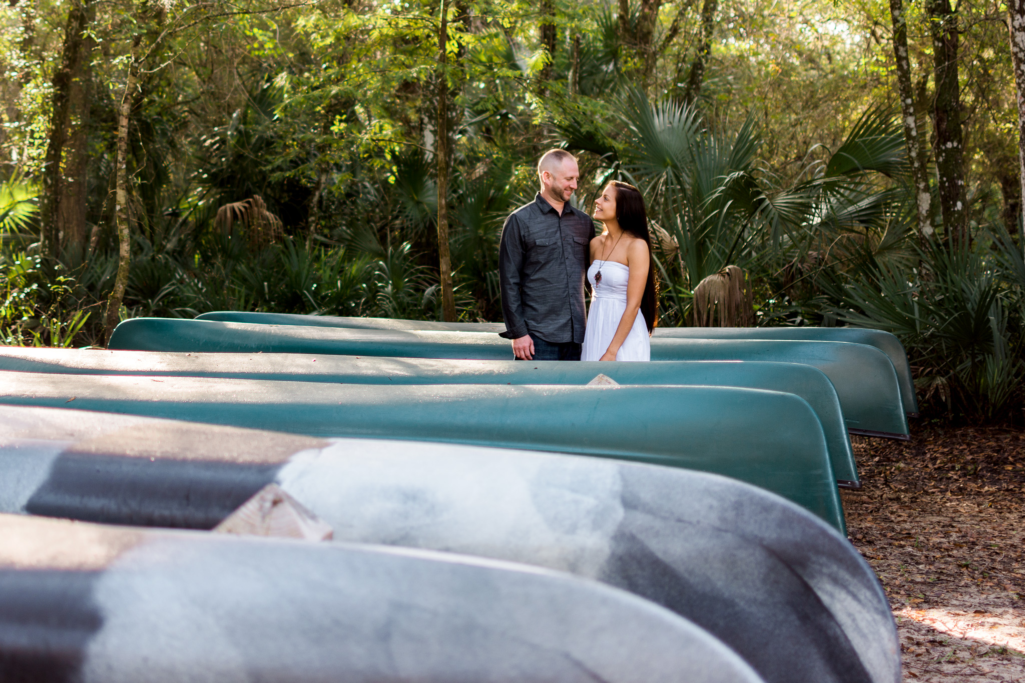Carlie Chew Photography captures loving couples portrait surrounded by kayaks at Lettuce Lake Park, Tampa, Florida