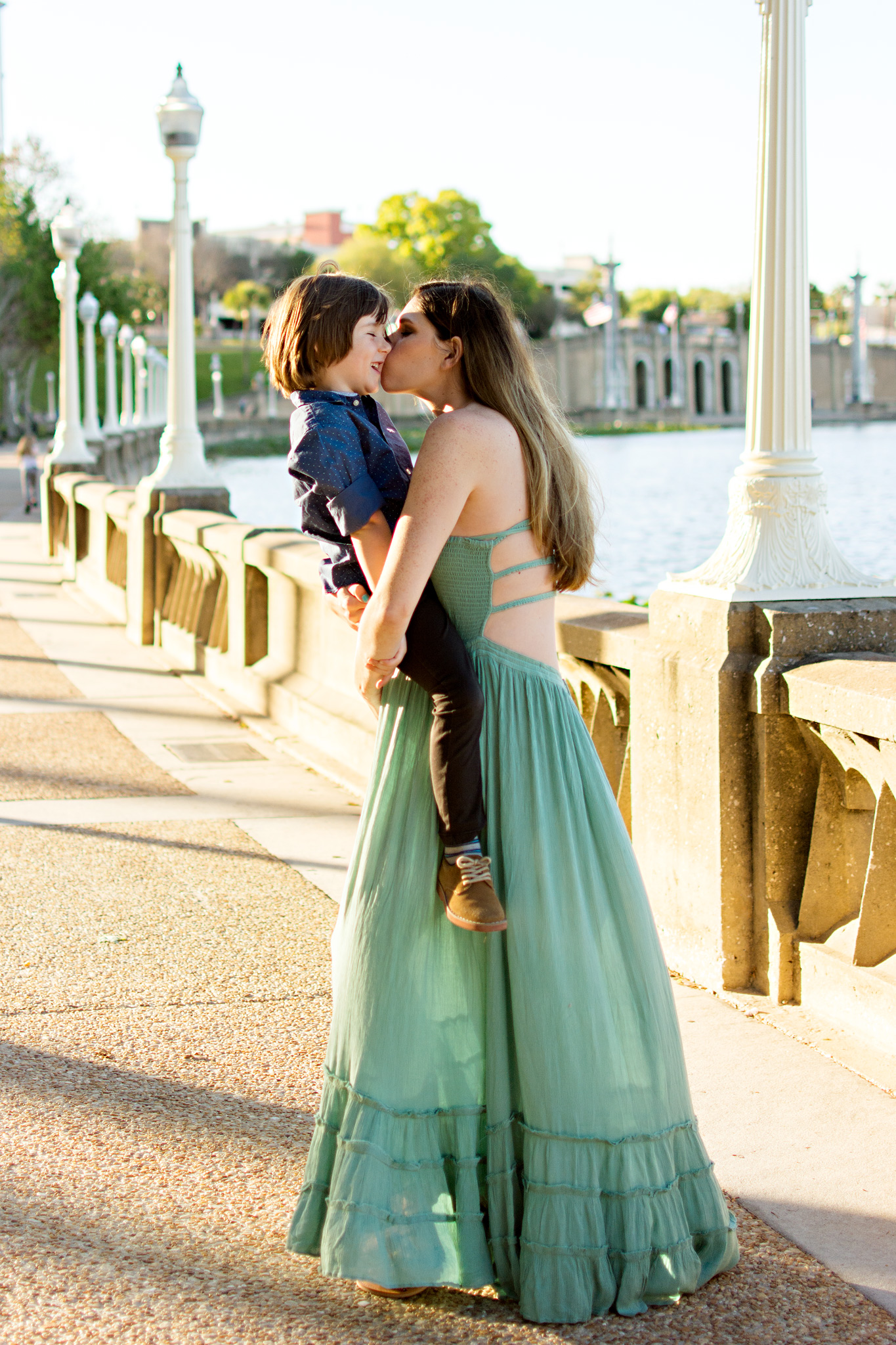 Pregnant mother hold son on her belly and kisses him at Mirror Lake, Lakeland FL with Carlie Chew Photography