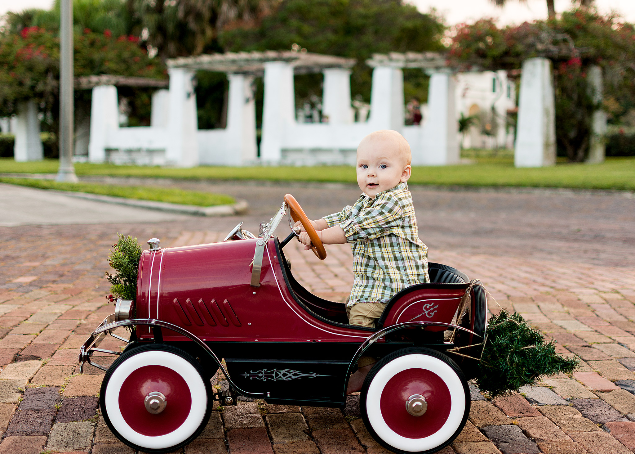 Baby boy in vintage red car with Christmas tree for holiday photos with Carlie Chew Photography in St. Petersburg FL