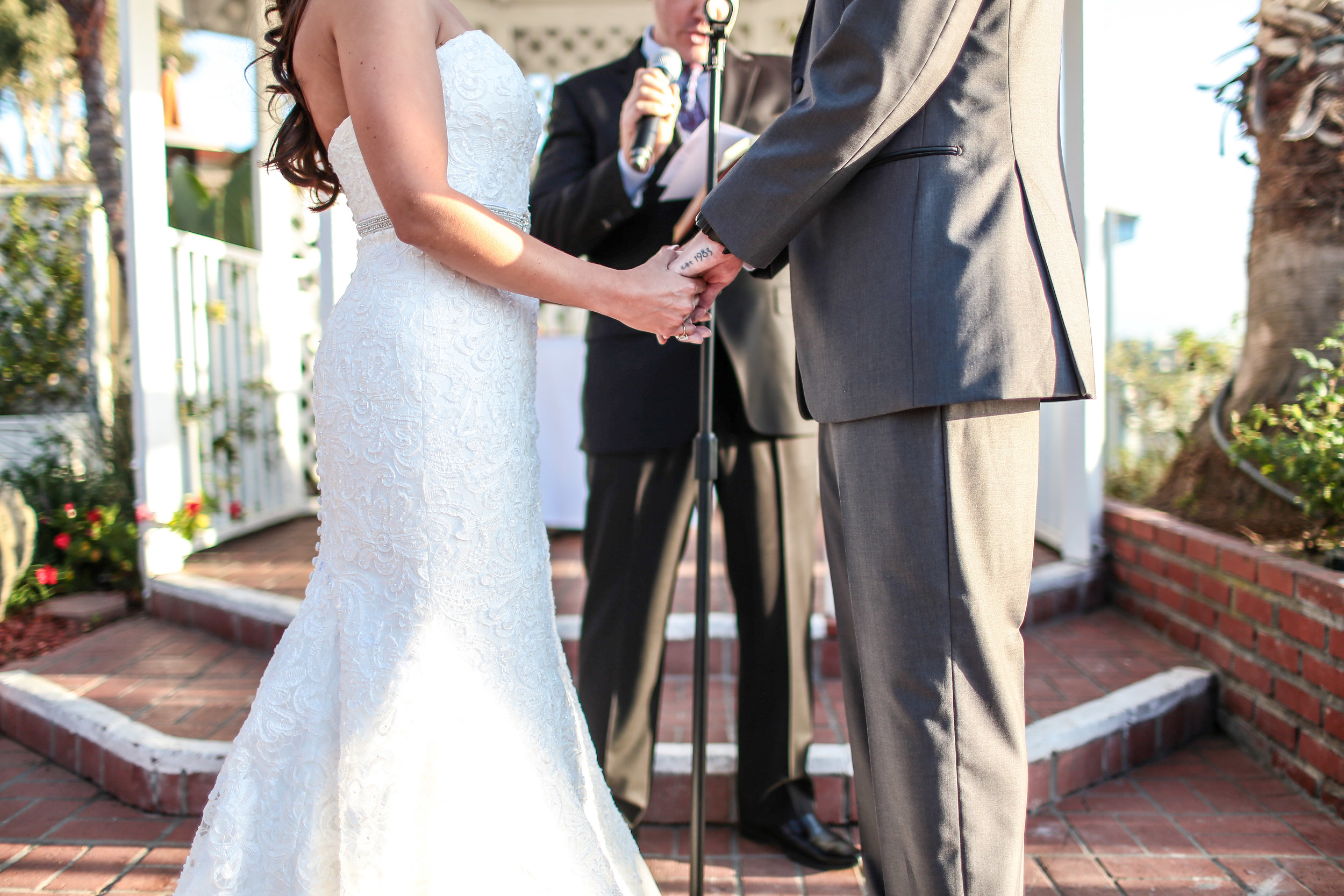 """Amanda and Eric hold hands as they are about to say """"I do"""" at their wedding by the beach in Marina del Rey."""