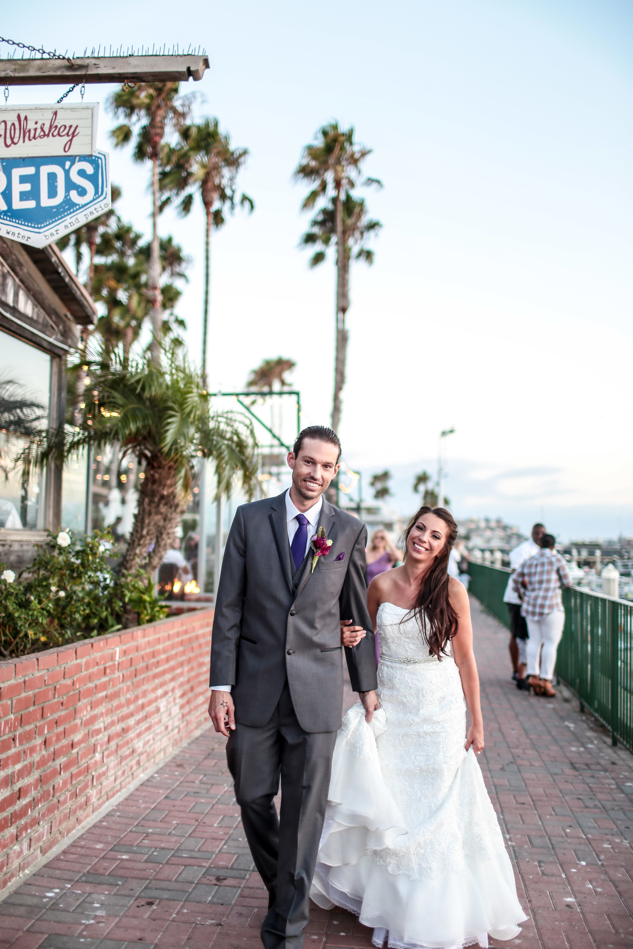 Amanda and Eric smile for the camera by the beach at their Marina del Rey wedding.