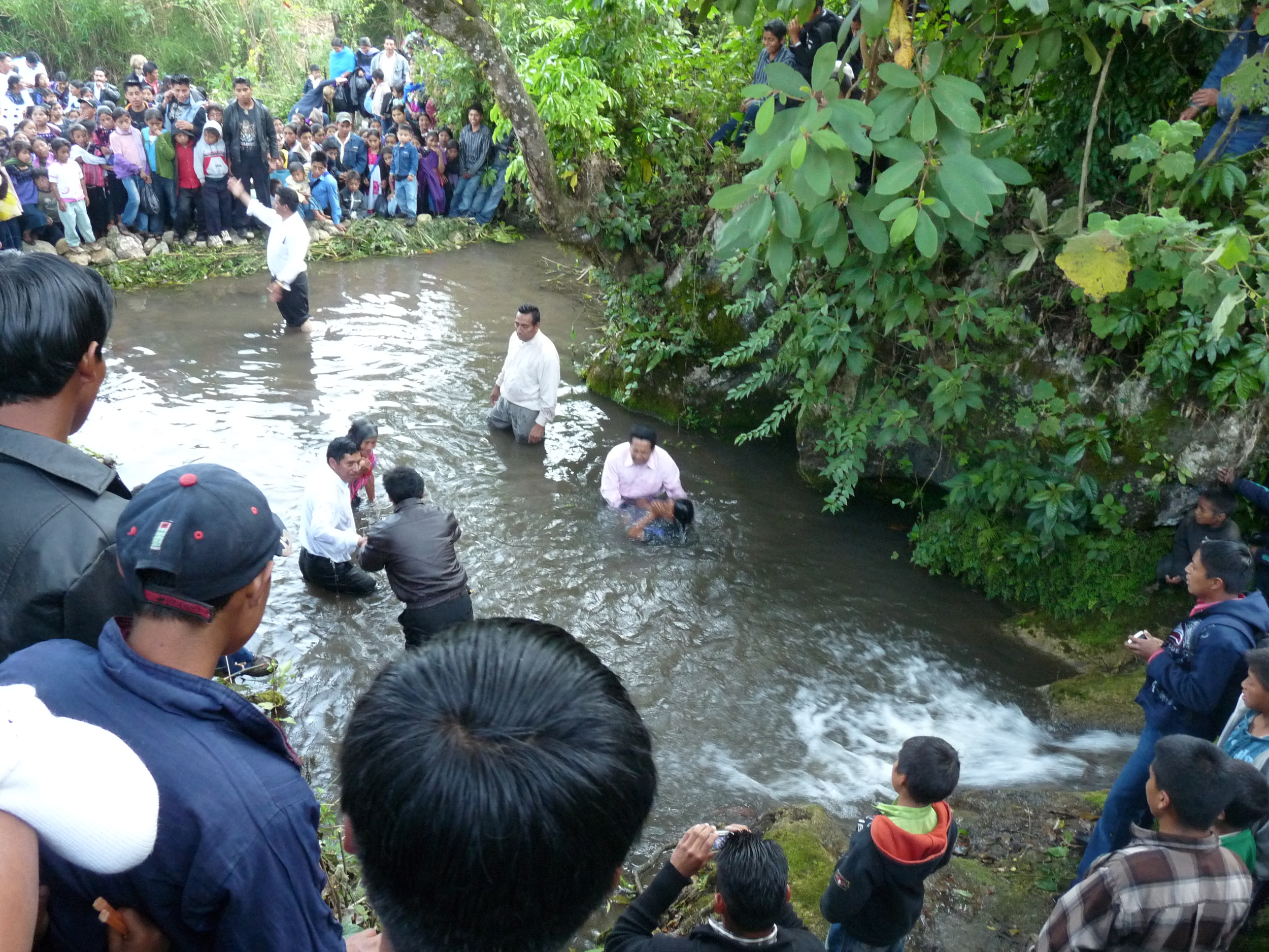 A crowd of indigenous mountain people gather at a river for baptism.