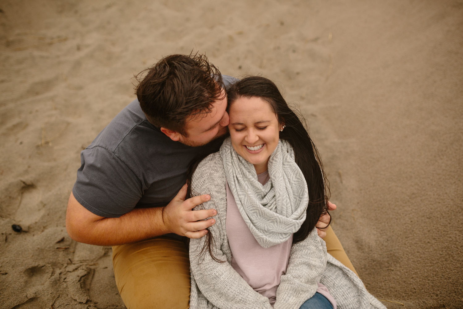 A happy couple cuddling on the sand