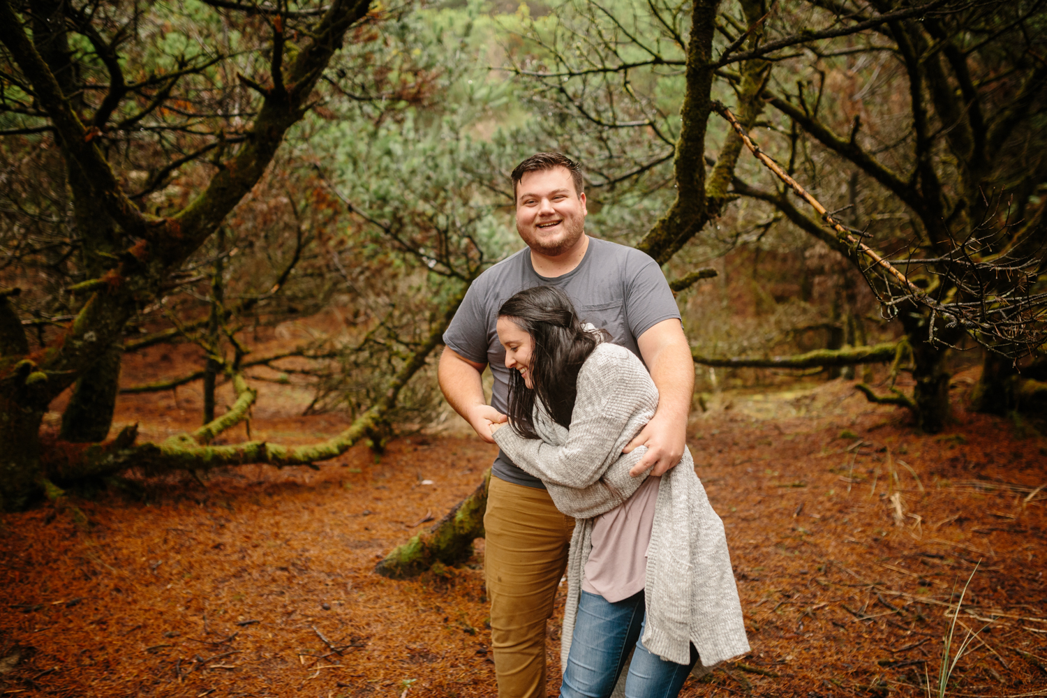 A happy young couple laughing and dancing amdist the trees near