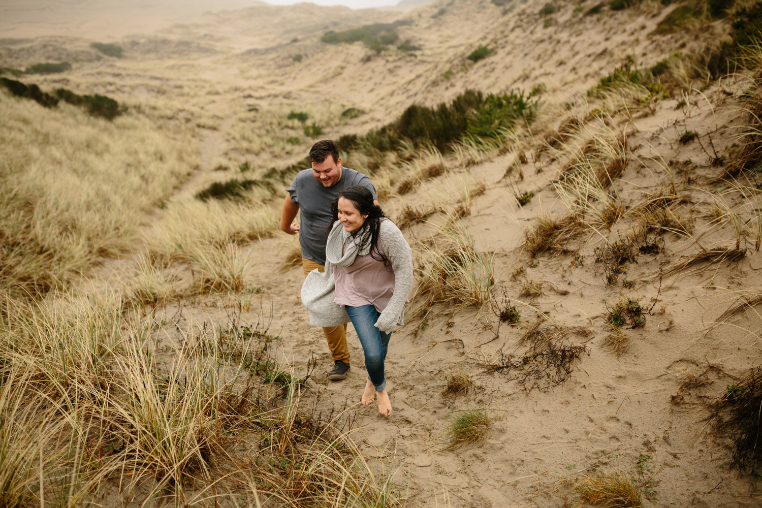 Portrait of a young couple walking through the sand and tall gra
