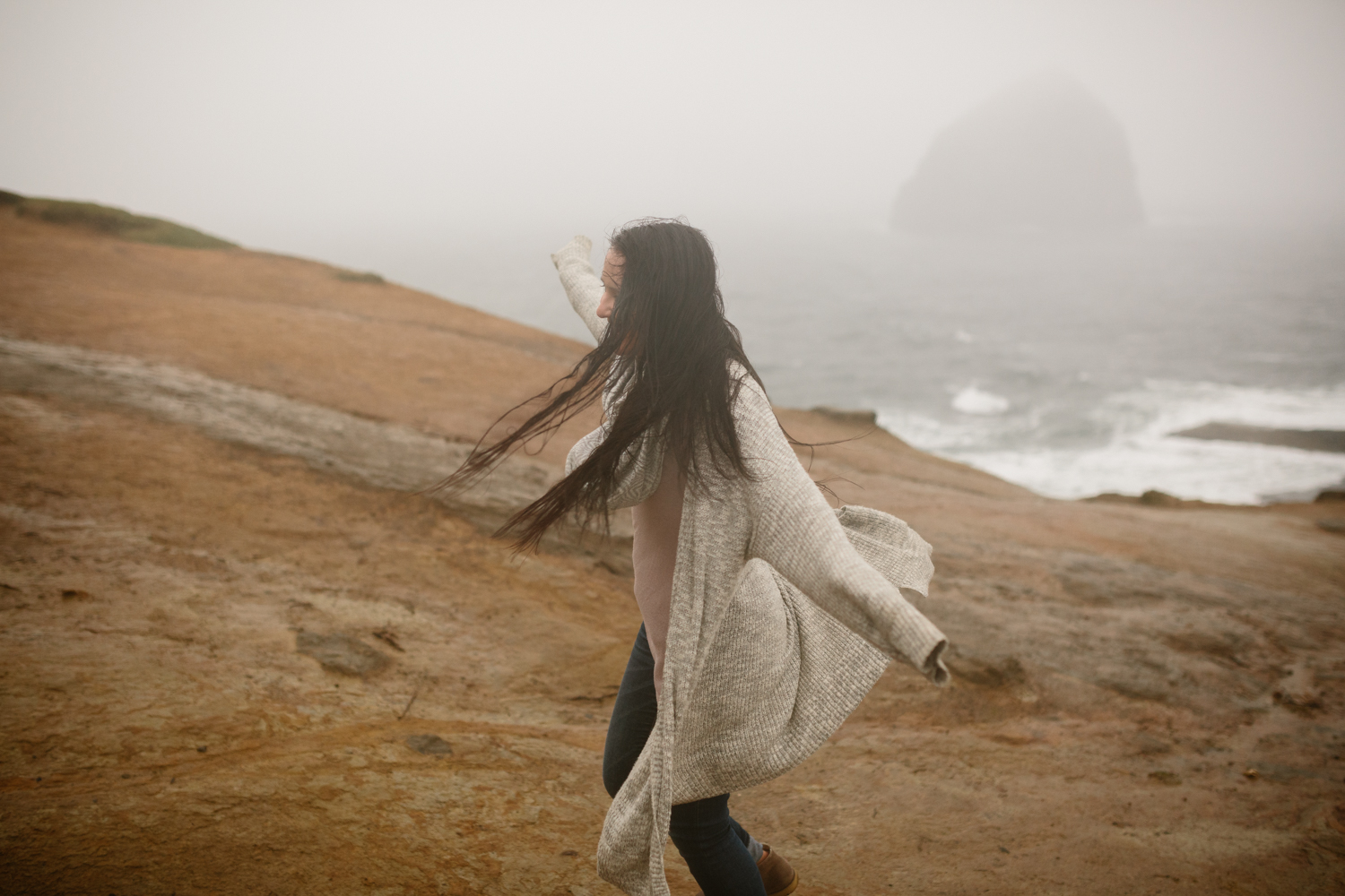 A portrait of young woman with wind blowing through her hair and