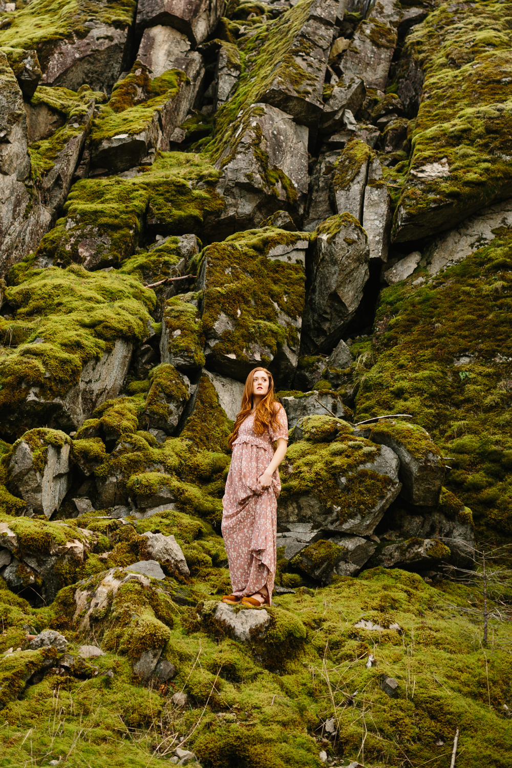 Portrait of a beautiful red-haired woman standing on mossy bould