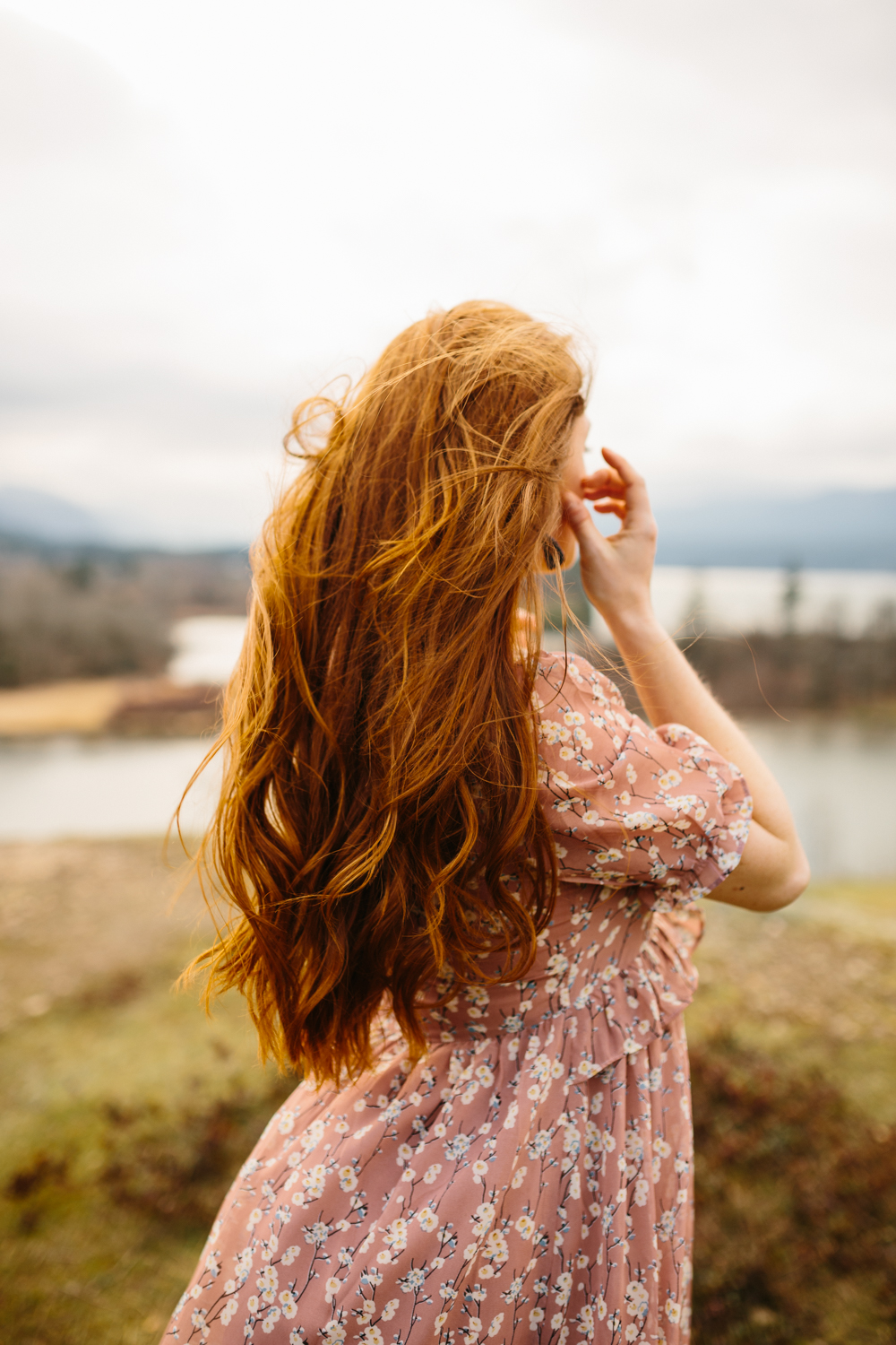 A Woman Brushing Hair From Her Face as the Wind Blows Through He