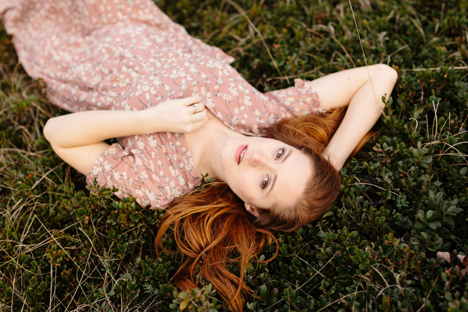 Portrait of a beautiful red-haired woman laying amidst succulent