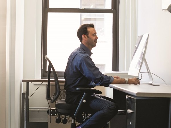 Office life. A man in casual clothing seated at a desk looking a