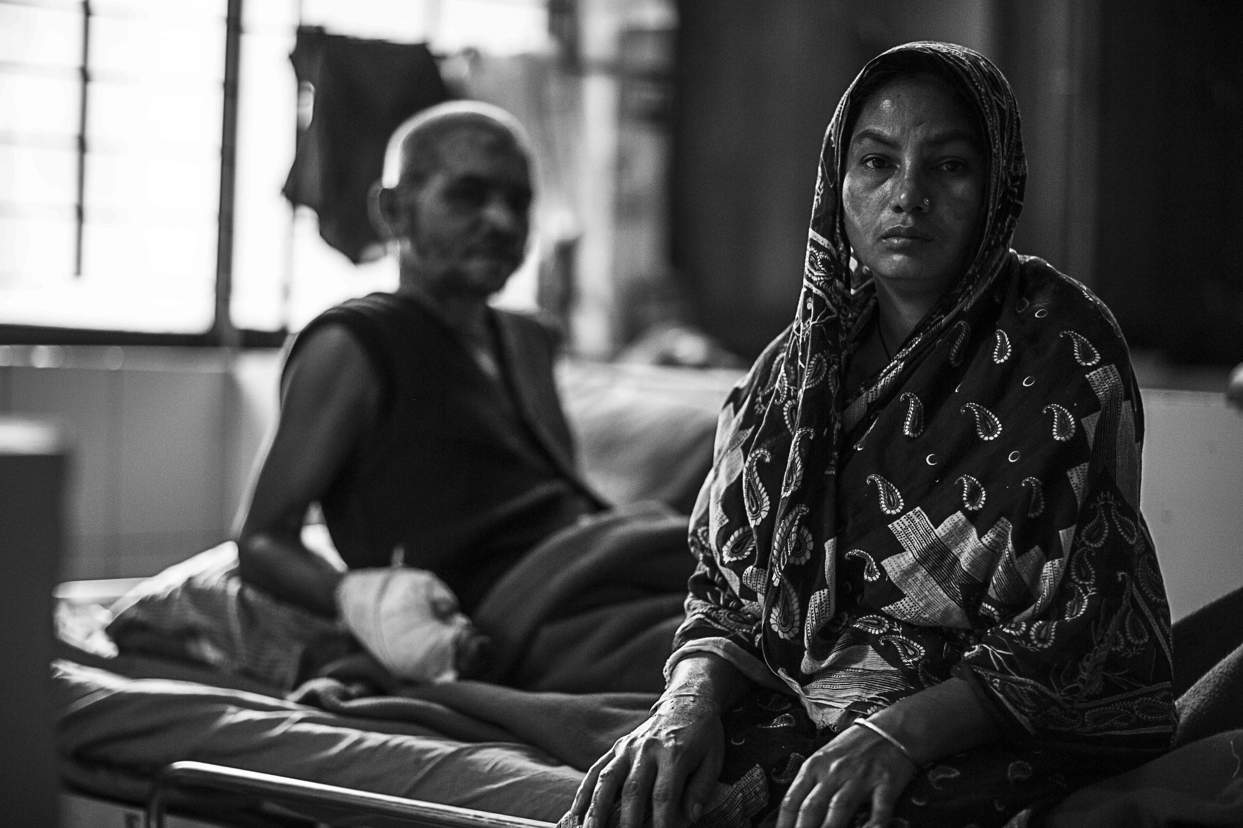 Sahira Khatun sits and waits patiently on her husband's bed. Days are long within the walls of DMCH.
