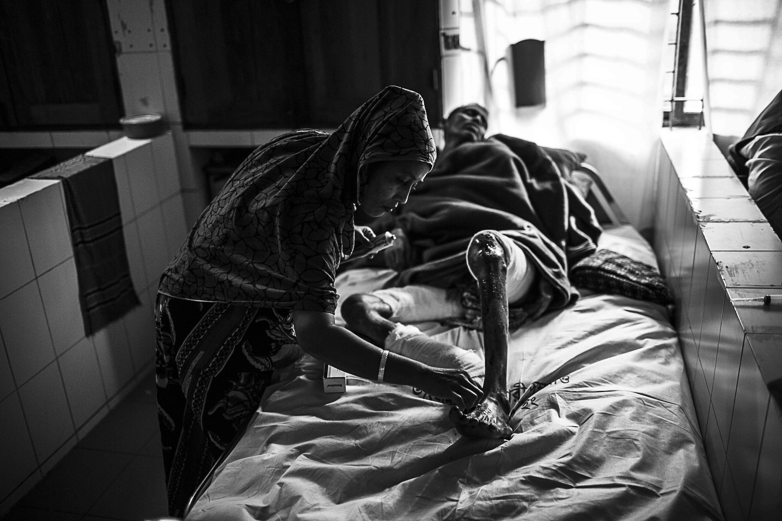 Nasima Begum tends to her husband, Mohammad. Some duties are left to family members instead of nurses.