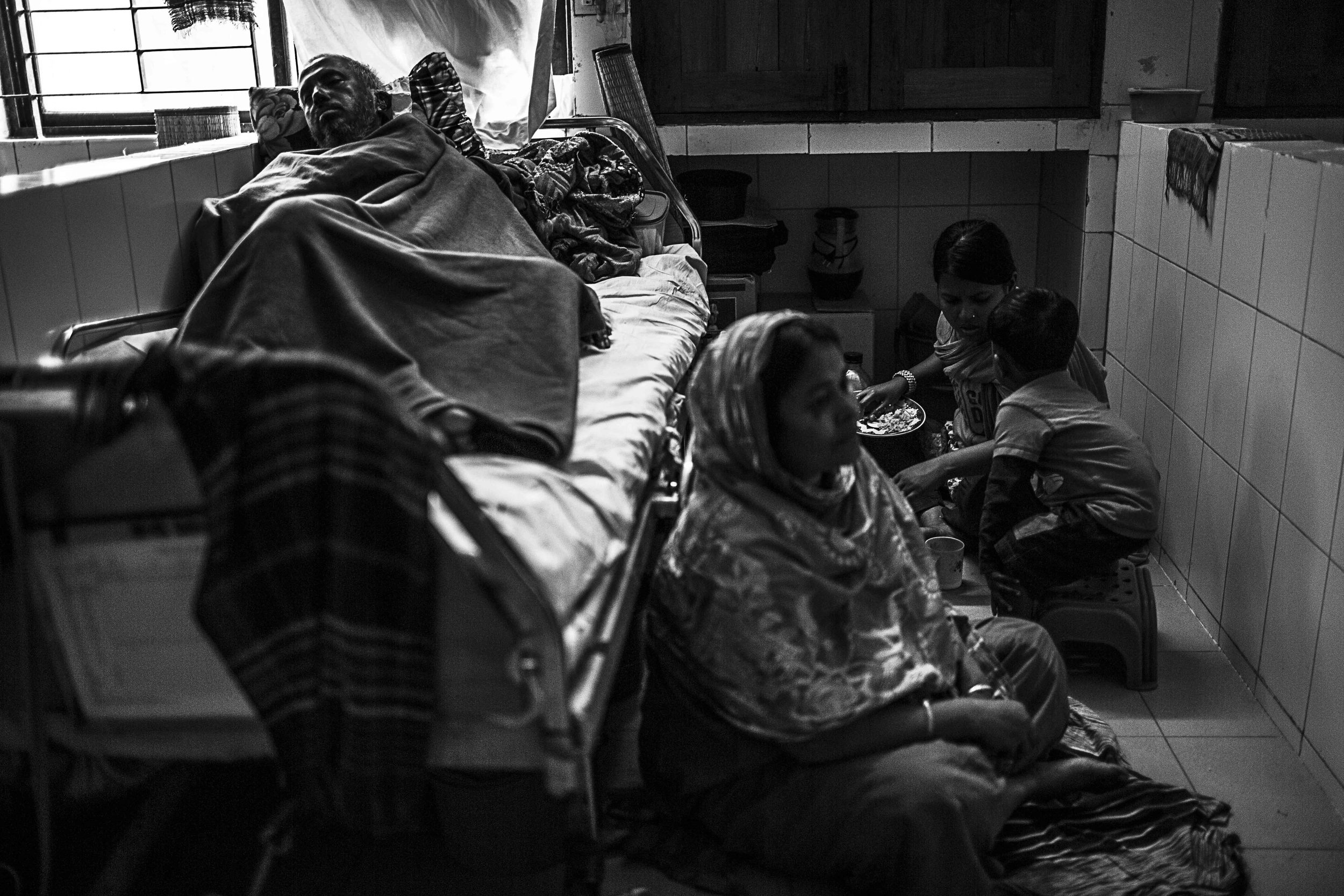 Korshed Alam takes some rest, while family members including his wife, Ms Shamunnahar sits on the floor and eat. Food is provided twice through the day to patients, if they require more – that is the job of family members to bring in.
