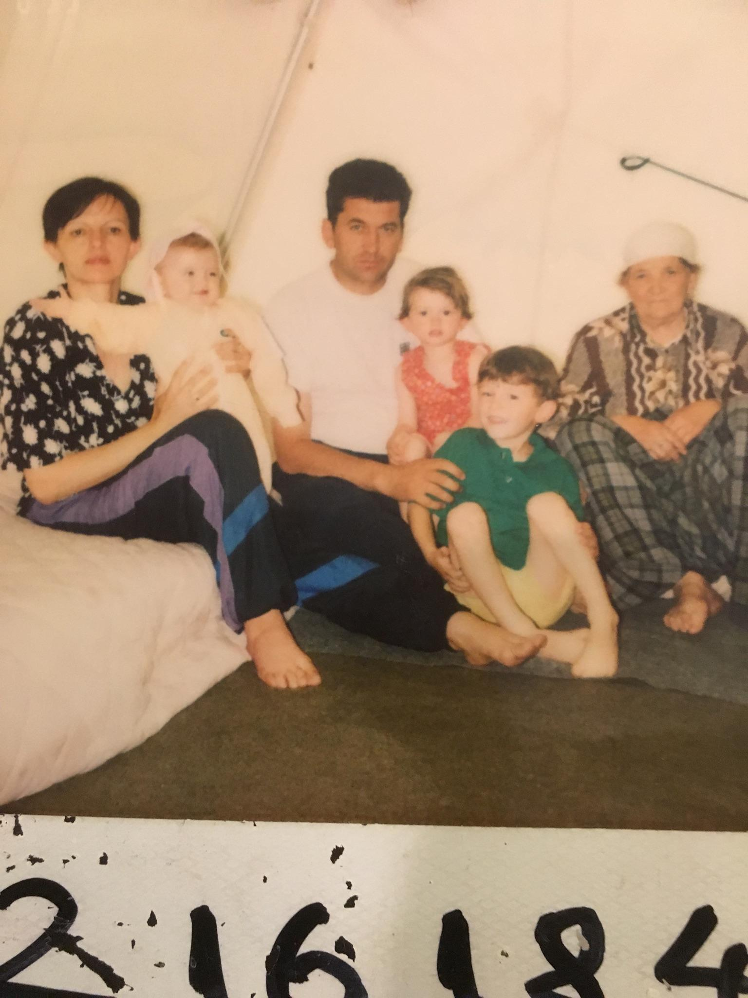 Petrit (center, in green shirt) in a refugee camp with his family.