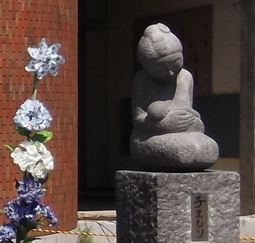 The Protective Mother statue in front of the tsunami-devastated Okawa Elementary School in Miyagi, Japan
