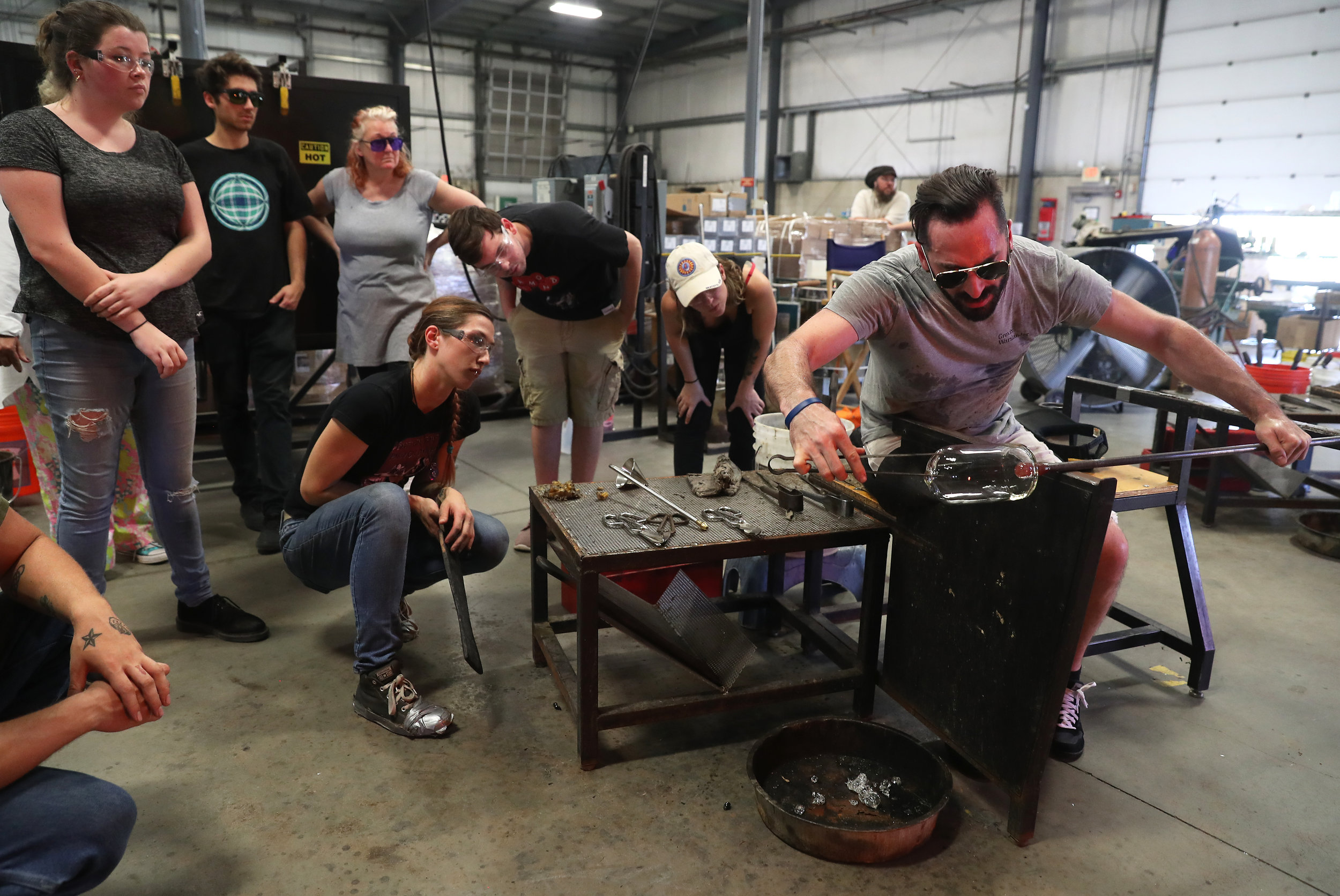 Instructor Alexander Rosenberg demonstrating how to create a glass cylinder in the hot shop.