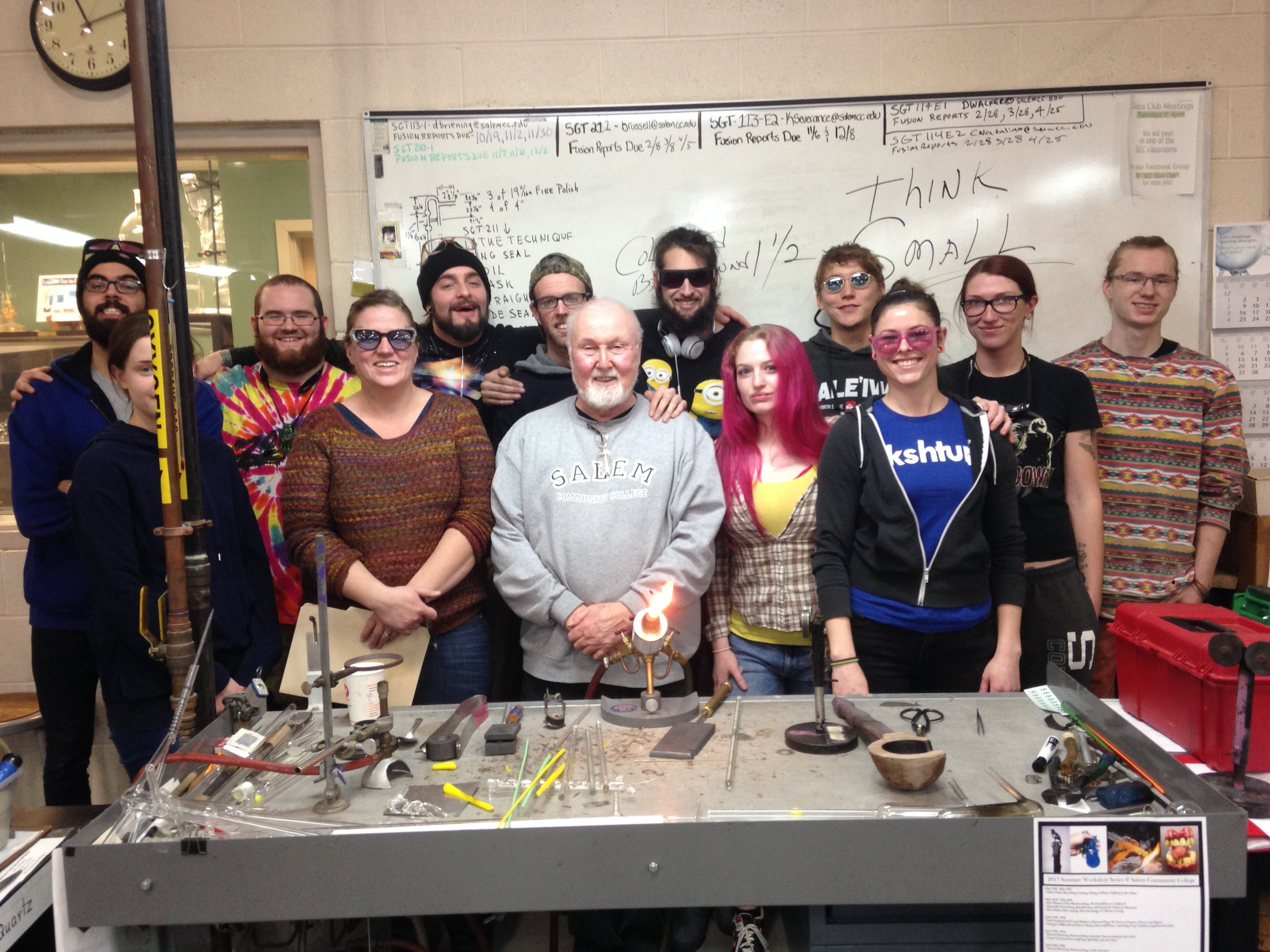 Artist in Residence Paul Stankard posing with students at the SCC Glass Education center after demonstrating glass encapsulation at the torch.