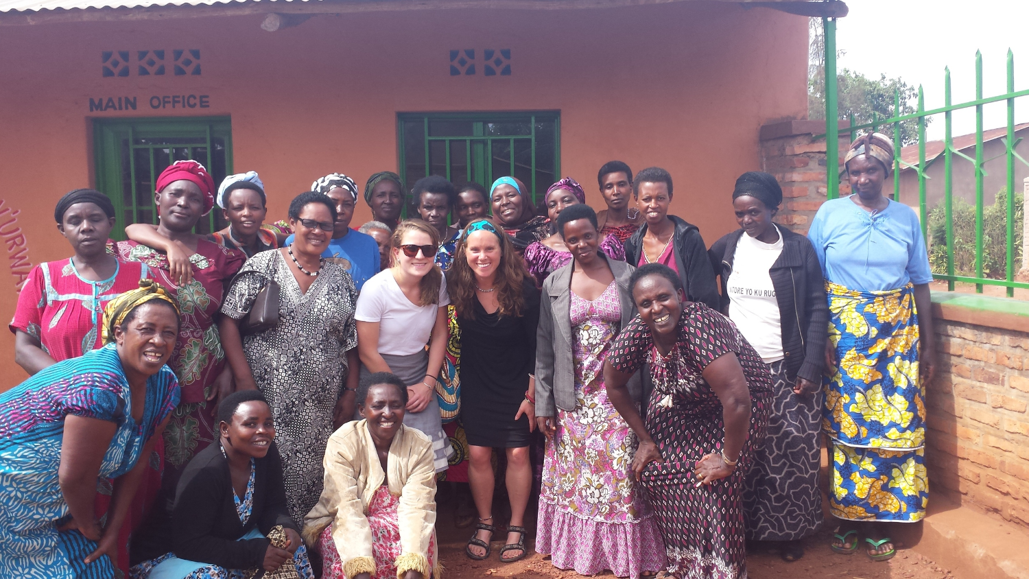 Flavia, pictured right in red & black dress, poses with her co-operative women, with Meg & Heather in Kayonza.