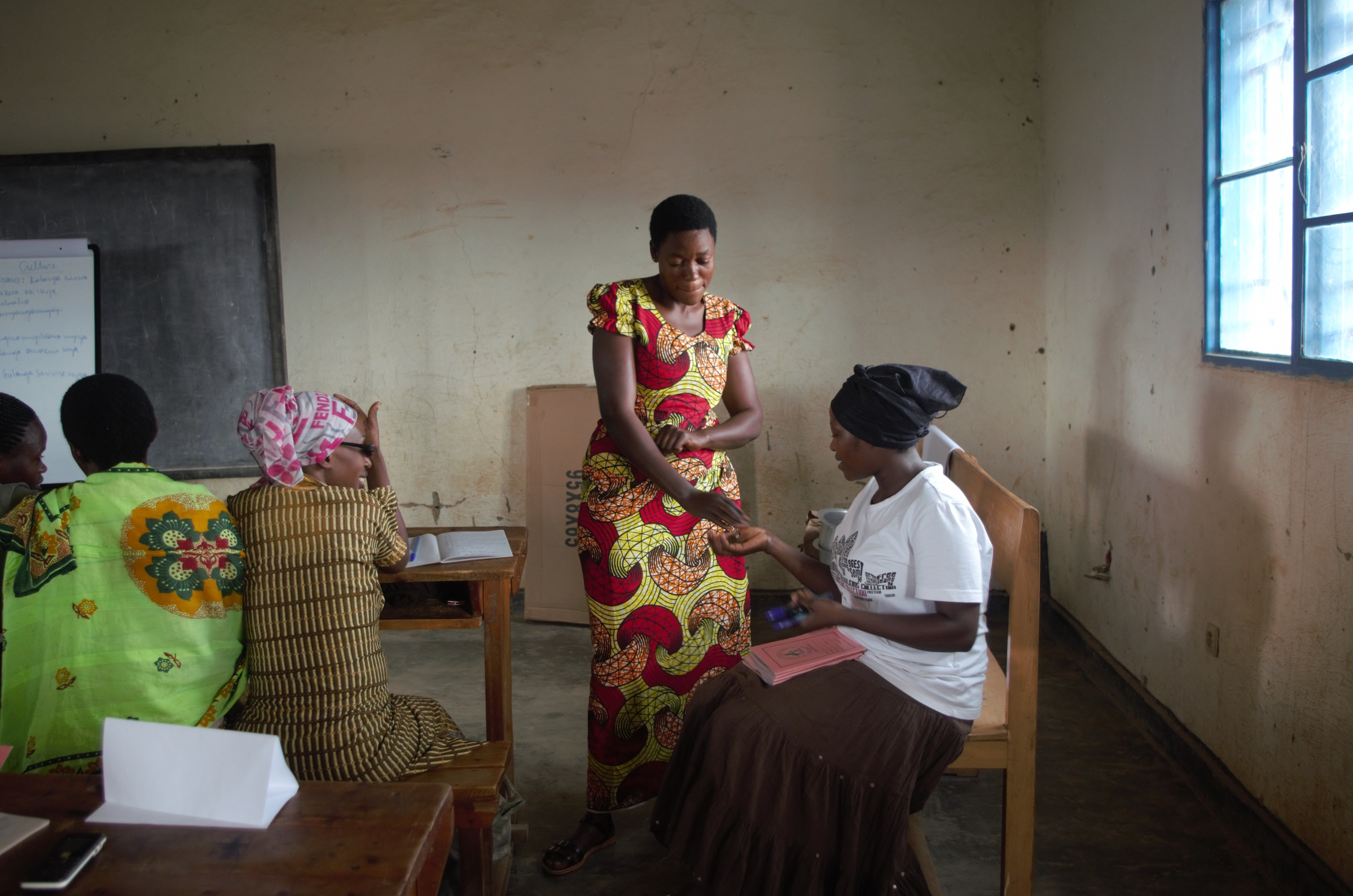 Jeanne D'Arc practicing the process of selling with fellow training participants in the Remera & Kanombe training group in Kigali.