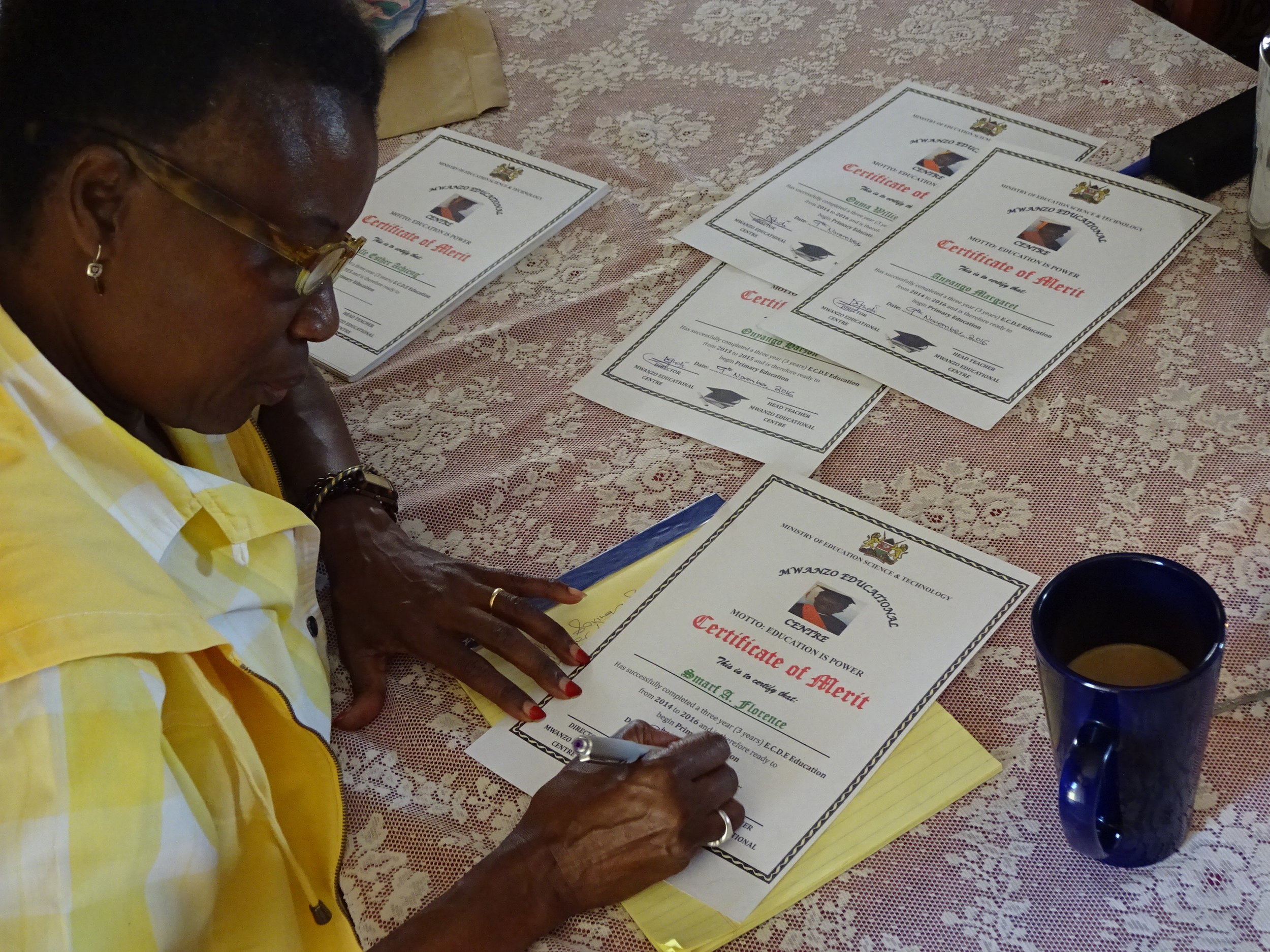 Loyce Signing Graduation Certificates