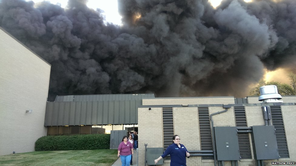 People hustle to exit the FlightSafetey International Building in Wichita, Kansas as a plane crashes on Thursday, killing four. Source: BBC
