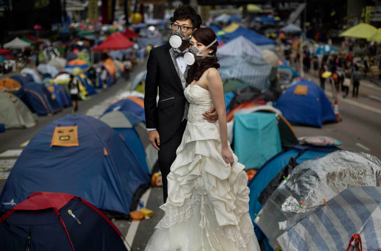 A newlywed couple wears gas masks while taking wedding photos beside pro-democracy demonstrators at the Admiralty protest site in Hong Kong. Source: Kevin Frayer/Getty Images.