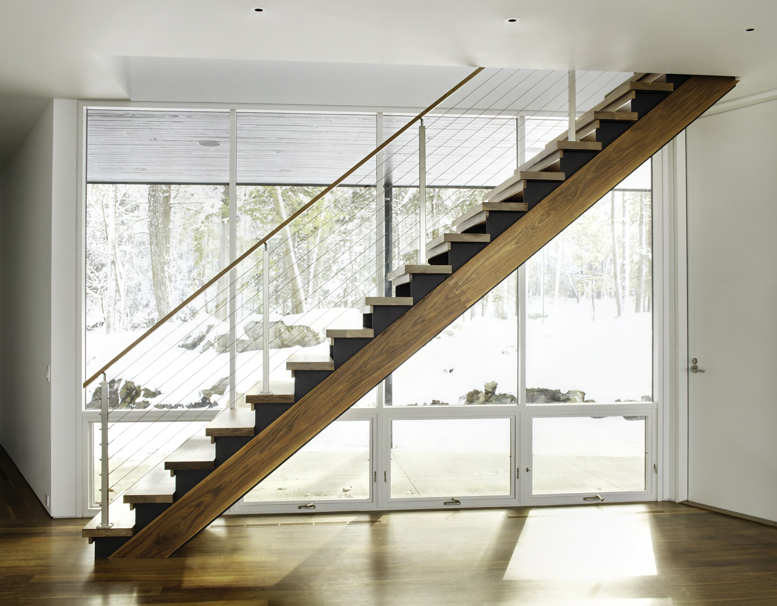gorgeous wooden staircase and large glass windows panoramic forest views