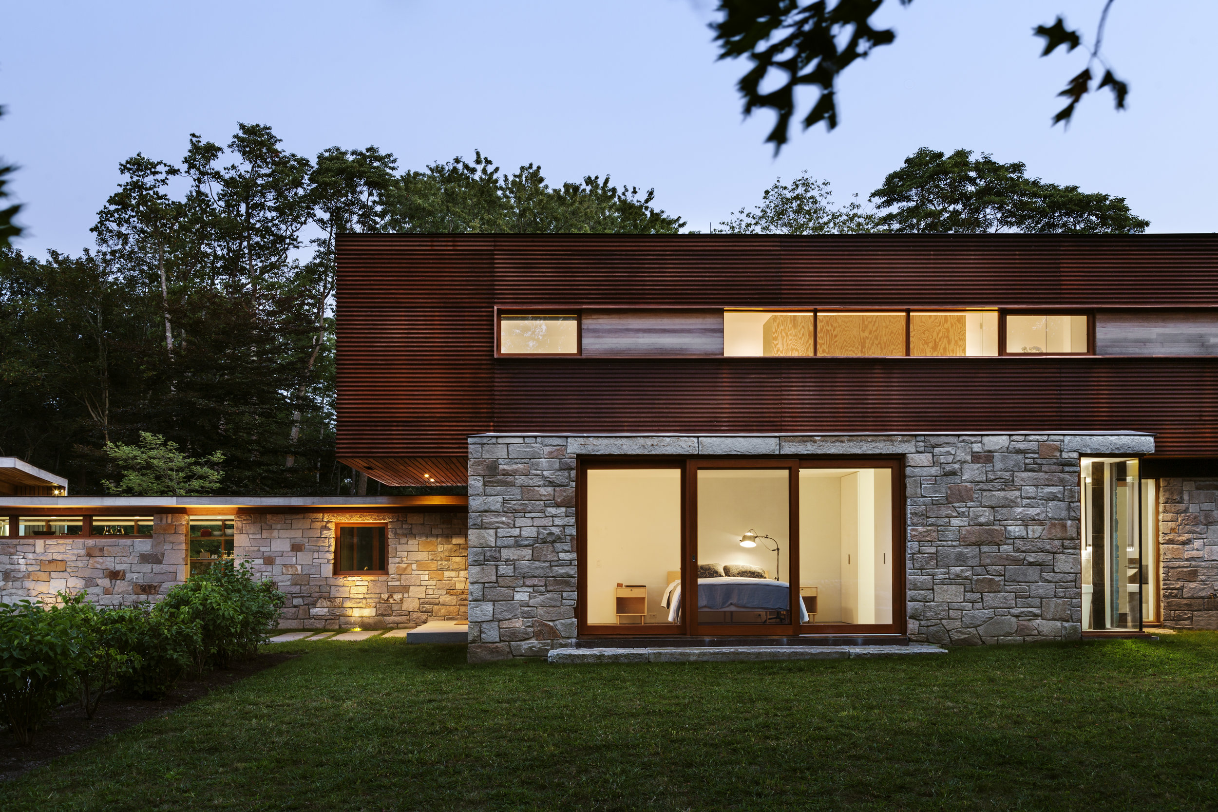 large glass windows with stone veneer and wood architecture