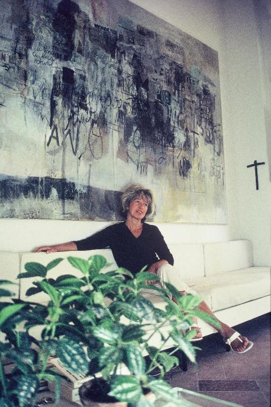 Sarah Grilo seating with one of her paintings,  Ni un día más  (1966), in the house that she designed in the south of Spain. Marbella, ca. 1970  Photo: Juan Muro © The Estate of Sarah Grilo