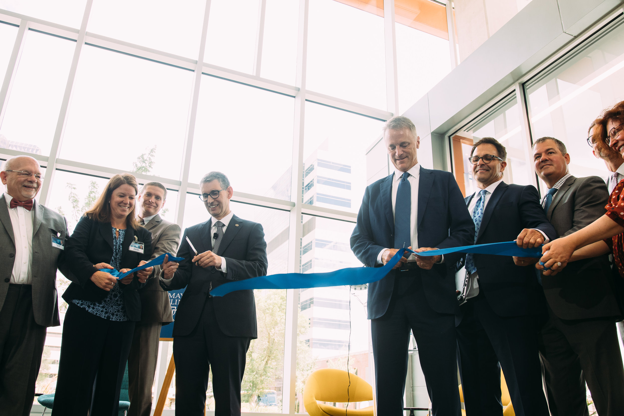Farrugia (center left) and Mahoney (center right) join in a ribbon cutting Monday at One Discovery Square in downtown Rochester.