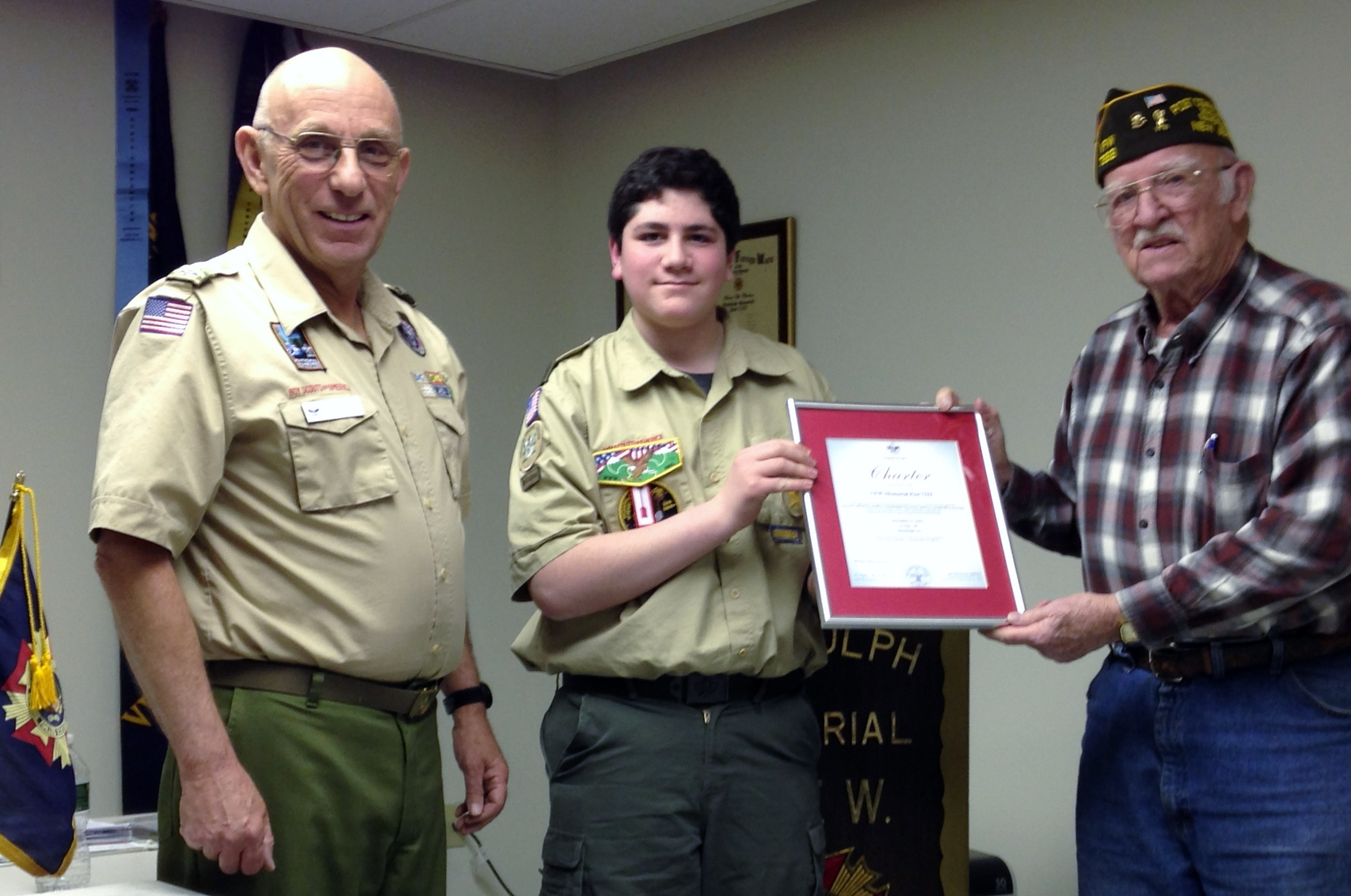 Scout Master Ken and  Troop 50 senior patrol leader Michael present the annual Boy Scout of America sponsor charter to past Post Commander Bob.