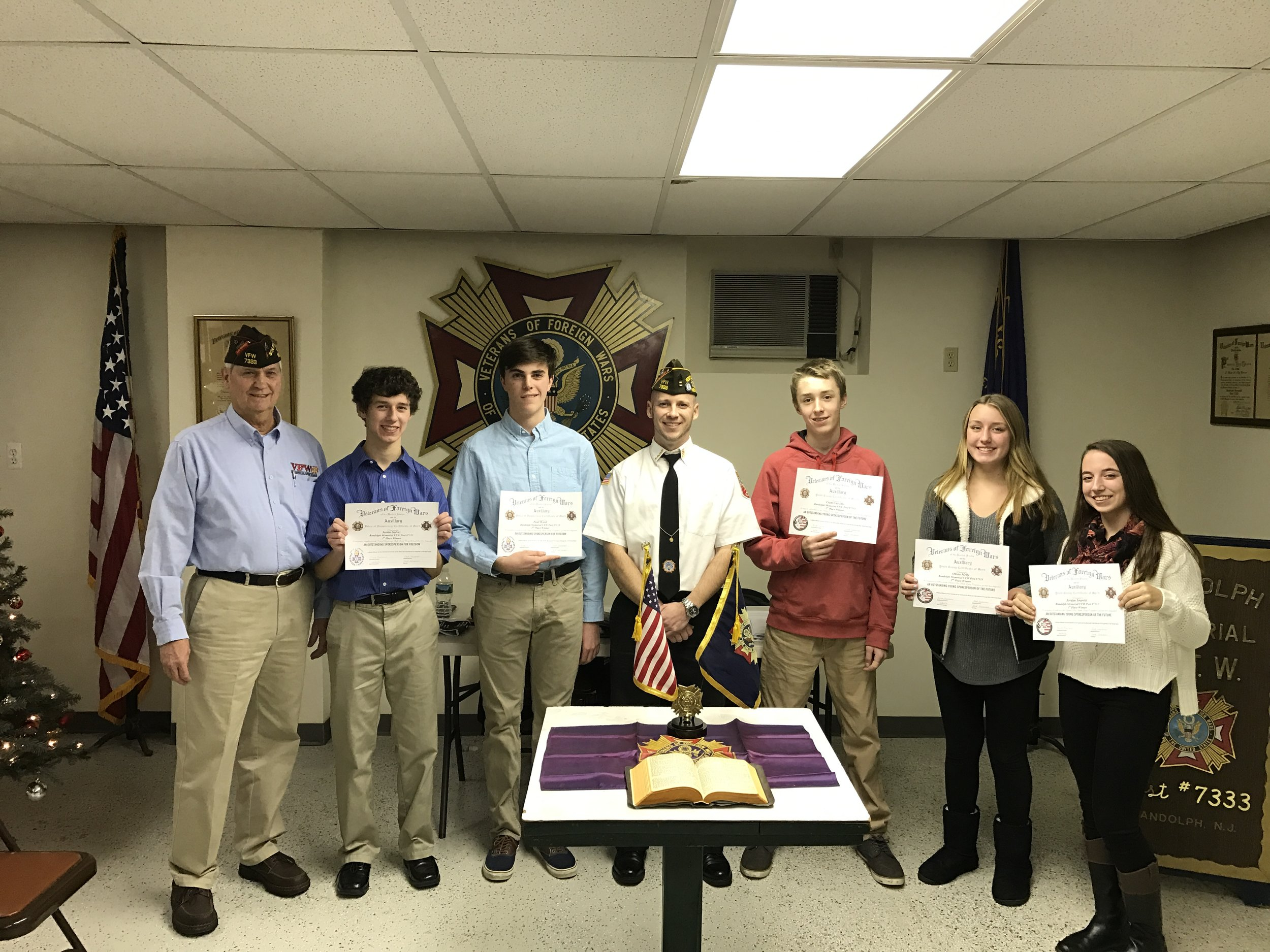 "On December 20 , 2016 Randolph Memorial VFW Post #7333 presented awards to the local finalists in the VFW Patriot's Pen and Voice of Democracy essay contests. The Patriot's Pen contest is open to all students in the 6th thru 8th grades. This year's theme was ""The America I Believe In"". First place was awarded to Jordan Snarski, 2nd place to Olivia Melly and 3rd to Liam Cassells. The Voice of Democracy contest is for high school students.This year's theme was ""My Responsibility To America"".The contest winner on the National level receives a scholarship of $30,000. First place for the Randolph area was awarded to Justin Galvez and Paul Ward received the 2nd place award. (pictured L-R: Program Chairman Jack Sassaman, Justin Galvez, Paul Ward, Post Commander Montanio, Liam Cassells, Olivia Melly, Jordan Snarski)."