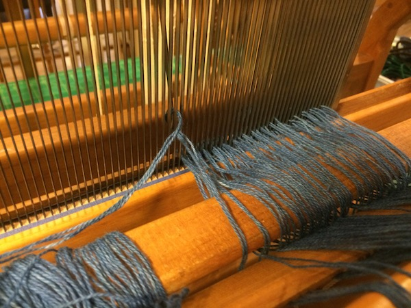 Our hand dyed indigo yarn being pulled through the reed.