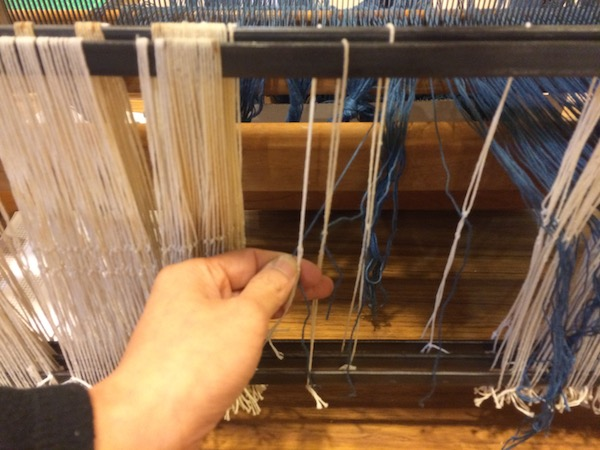 After we are finished threading the reed, we pull the indigo warp yarns through the homemade heddles.