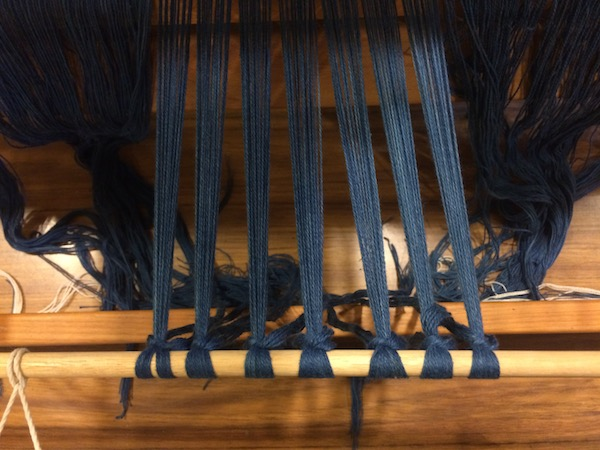 Tightening the warp yarns on the loom.