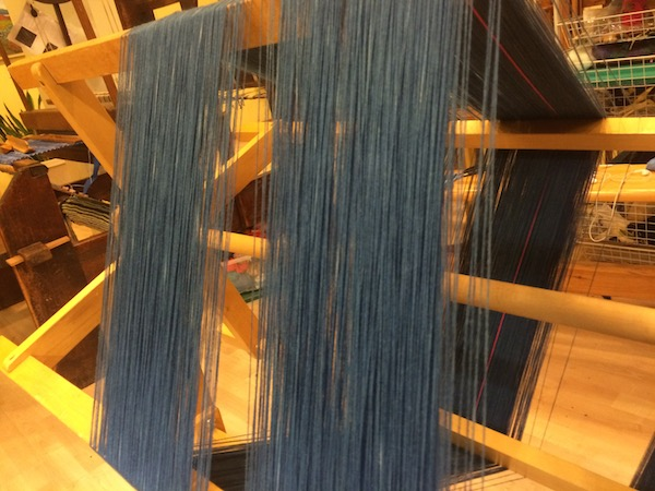 Organic cotton yarns dyed in indigo, on a warping frame.