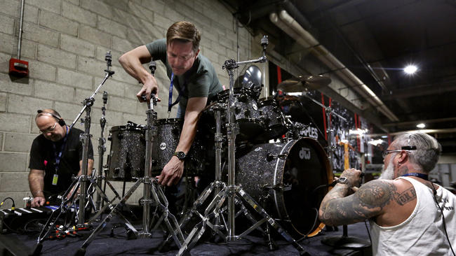 From left: Audio assistant Pete San Filipo, back line tech Ben Fenton and audio assistant Damon Andres get gear set up and check microphones on a drum riser that will be used for a performance by Lionel Richie during the Grammy Awards show.(Mel Melcon / Los Angeles Times)