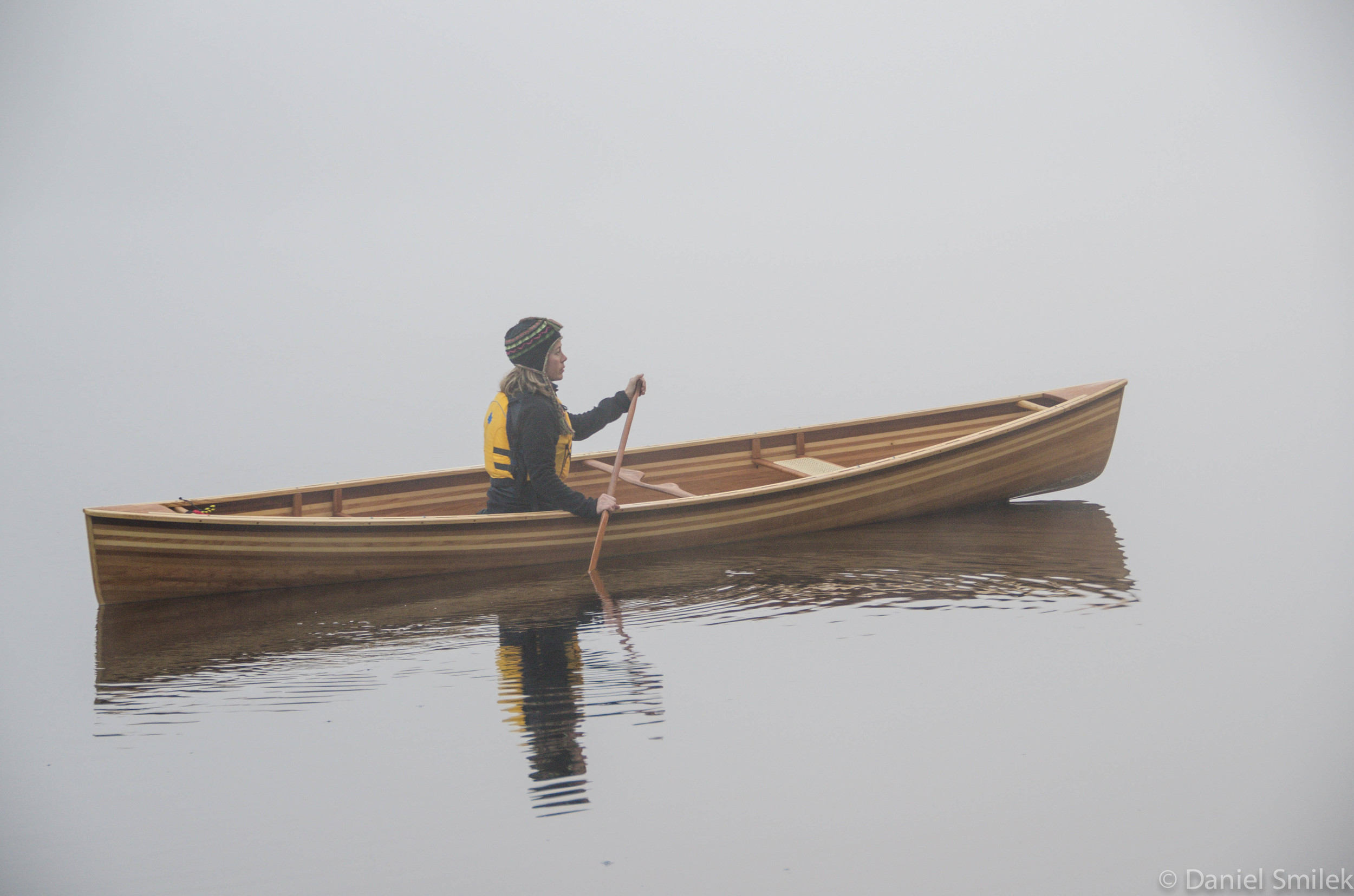 Shelley paddling the cedar strip Kipawa on a misty morning in Algonquin Park.