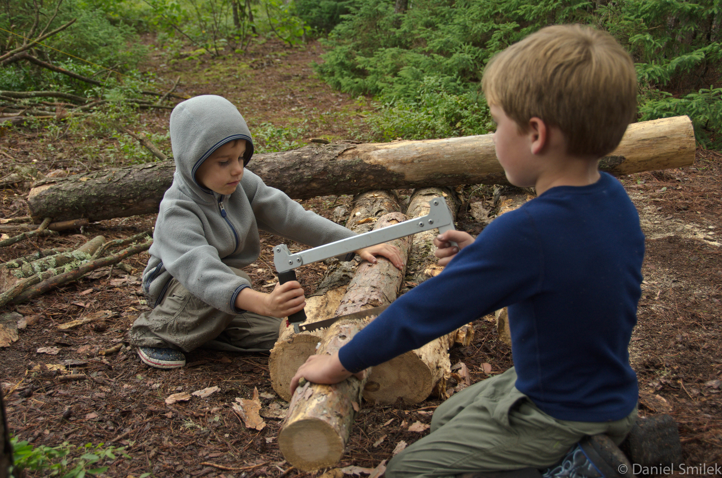 Luke (right) cutting wood with Noah (left).