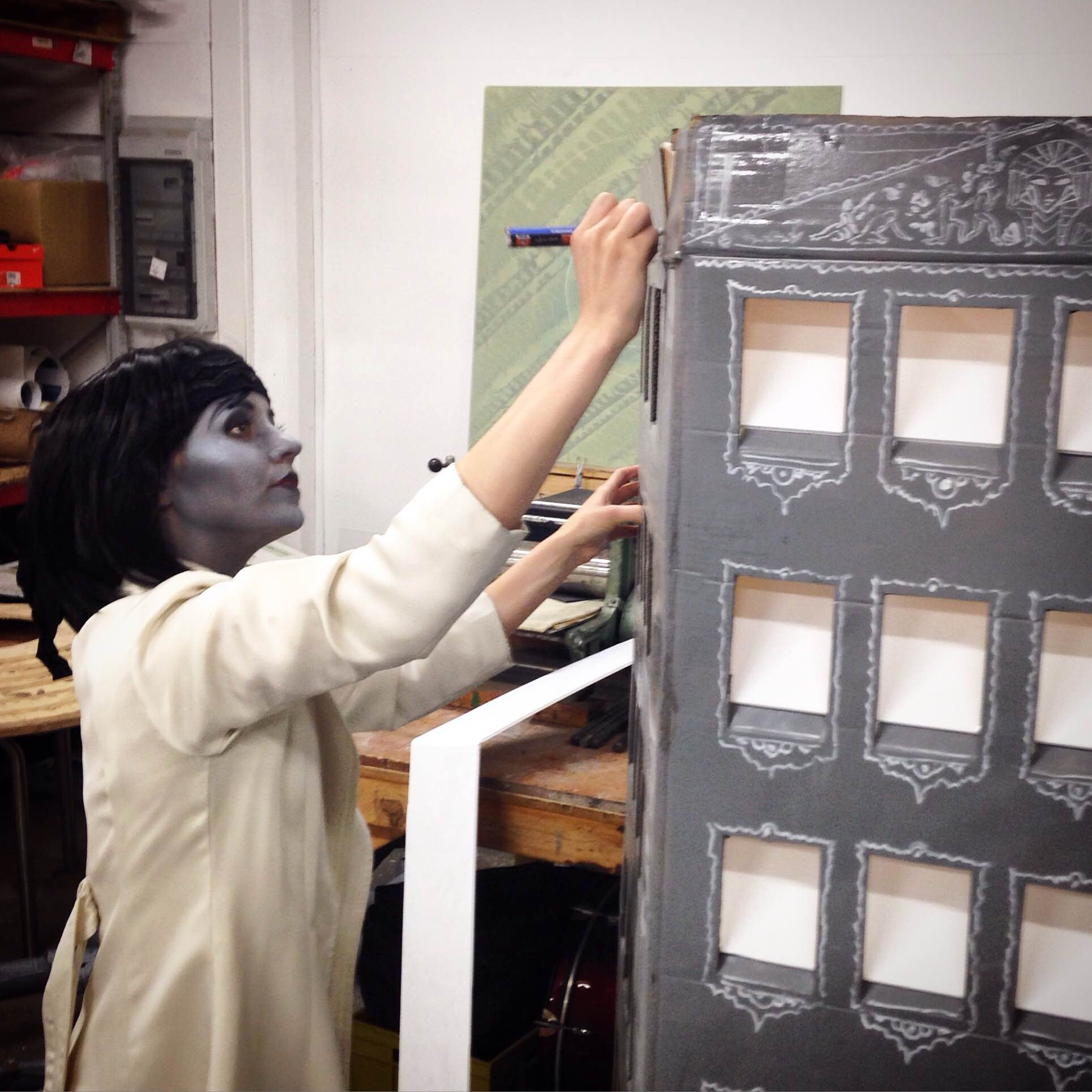 Above: The beautiful and insanely talented  Carolin Prinn  decorates some of the set's buildings.