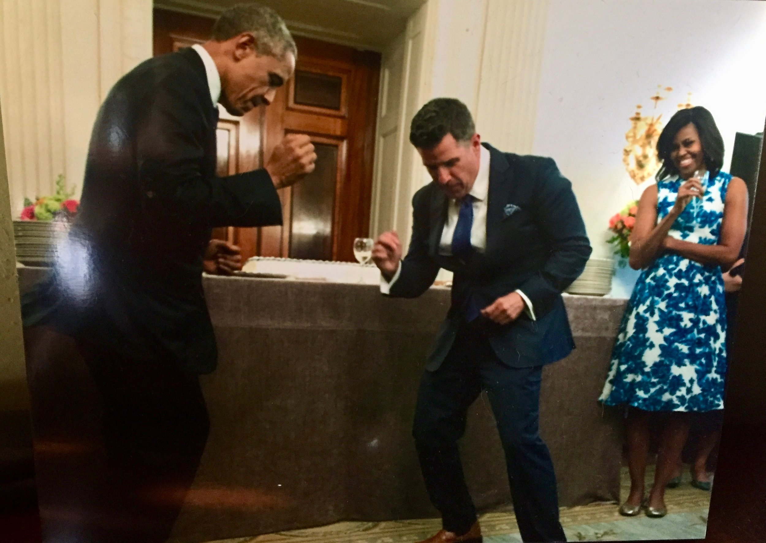 """This is a photo Dennis took of a photo in Jeremy's home. The President and Jeremy doing the """"Jeremy dance"""" together while Michelle Obama looks on and laughs."""