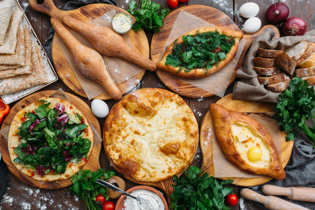 Traditional Georgian adjara khachapuri and Kolkh khachapuri on t
