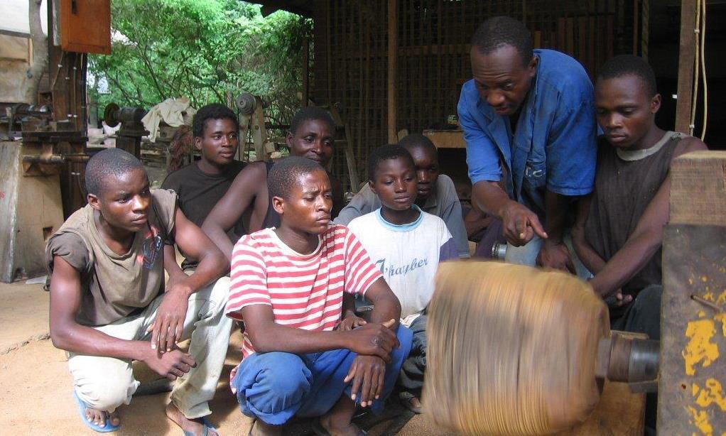 A ensinar jovens membros da comunidade como identificar a madeira para torneados  - Teaching young members of the local community how to do wood turning.