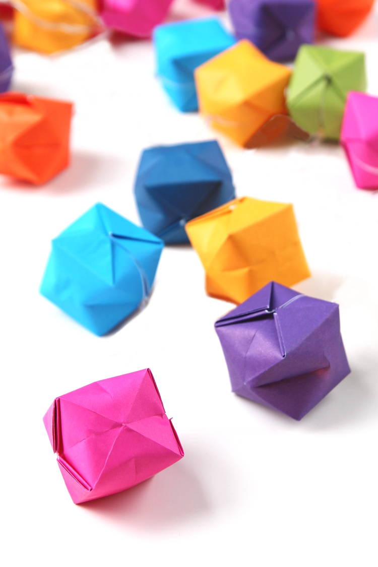 Learn how to make an origami water bomb from paper. A quick and fun project to make this summer. Fold them, fill with water and have fun throwing them as you chase down your friends and family #origami #waterbomb #kidscrafts #waterballoon