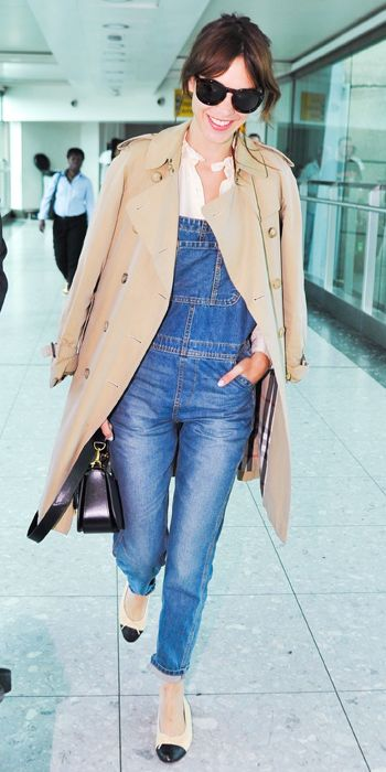 A pair of Chanel flats, a Burberry trench perfectly dress up a pair of overalls at the airport. Image via  InStyle