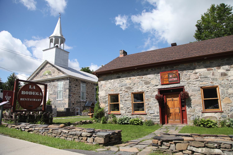 Notre restaurant se retrouve dans le belle demeure en pierre connue sous le nom de la  Maison Maynard , construite en 1832 par Samuel Maynard originaire du Vermont. Cette maison a servie de résidence et de bureau de poste de 1913 à 1927.