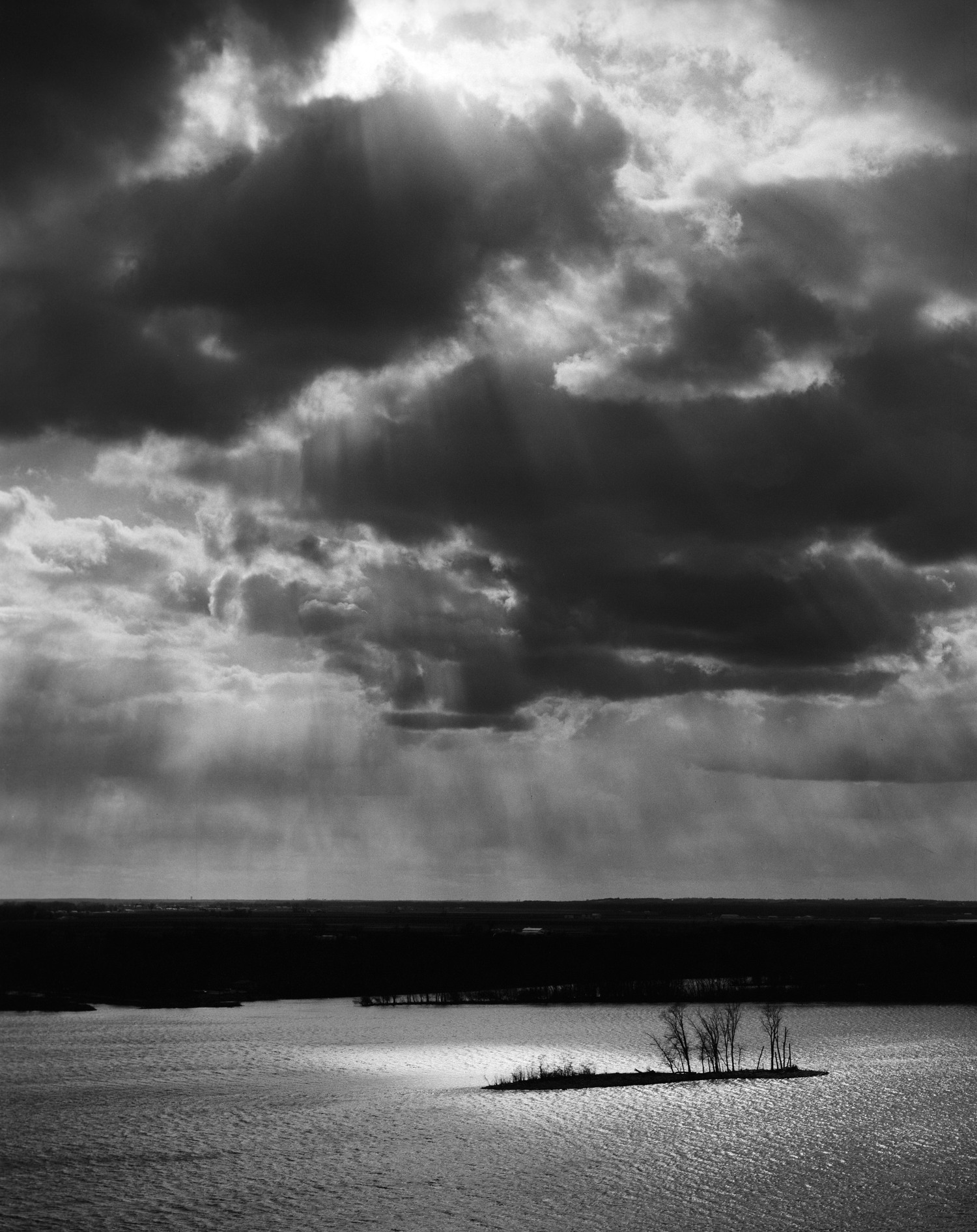 Godray over Elsah bar, Elsah IL 2012. A surprisingly mild Illinois winter was leading into a wet spring causing constant tumultuous clouds to stroll across the Mississippi River. I setup this frame with my Pentax 6x7 and waited about half an hour for a godray to illuminate the lone bar in the river.