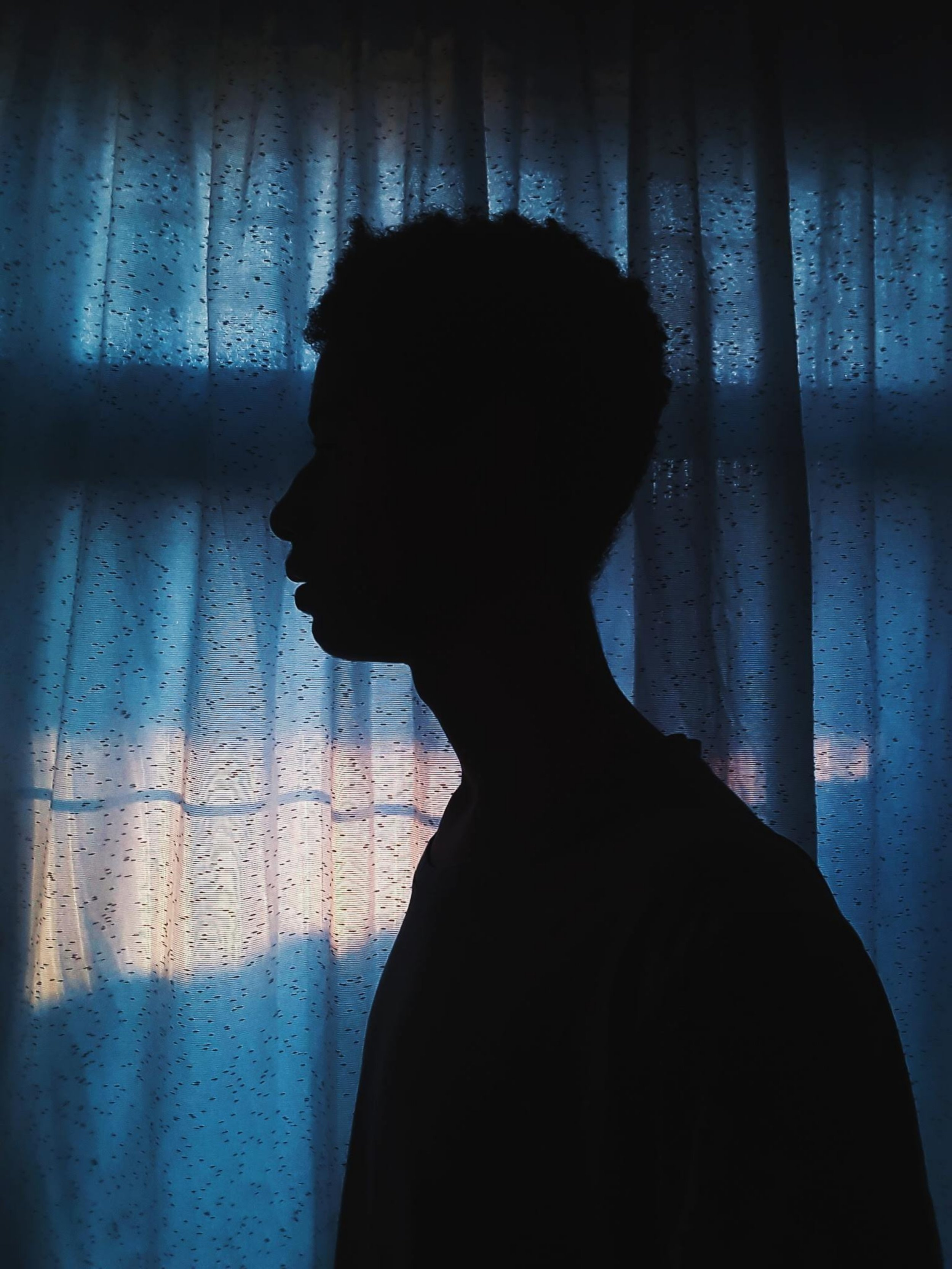 shadow of a man in front of a curtain