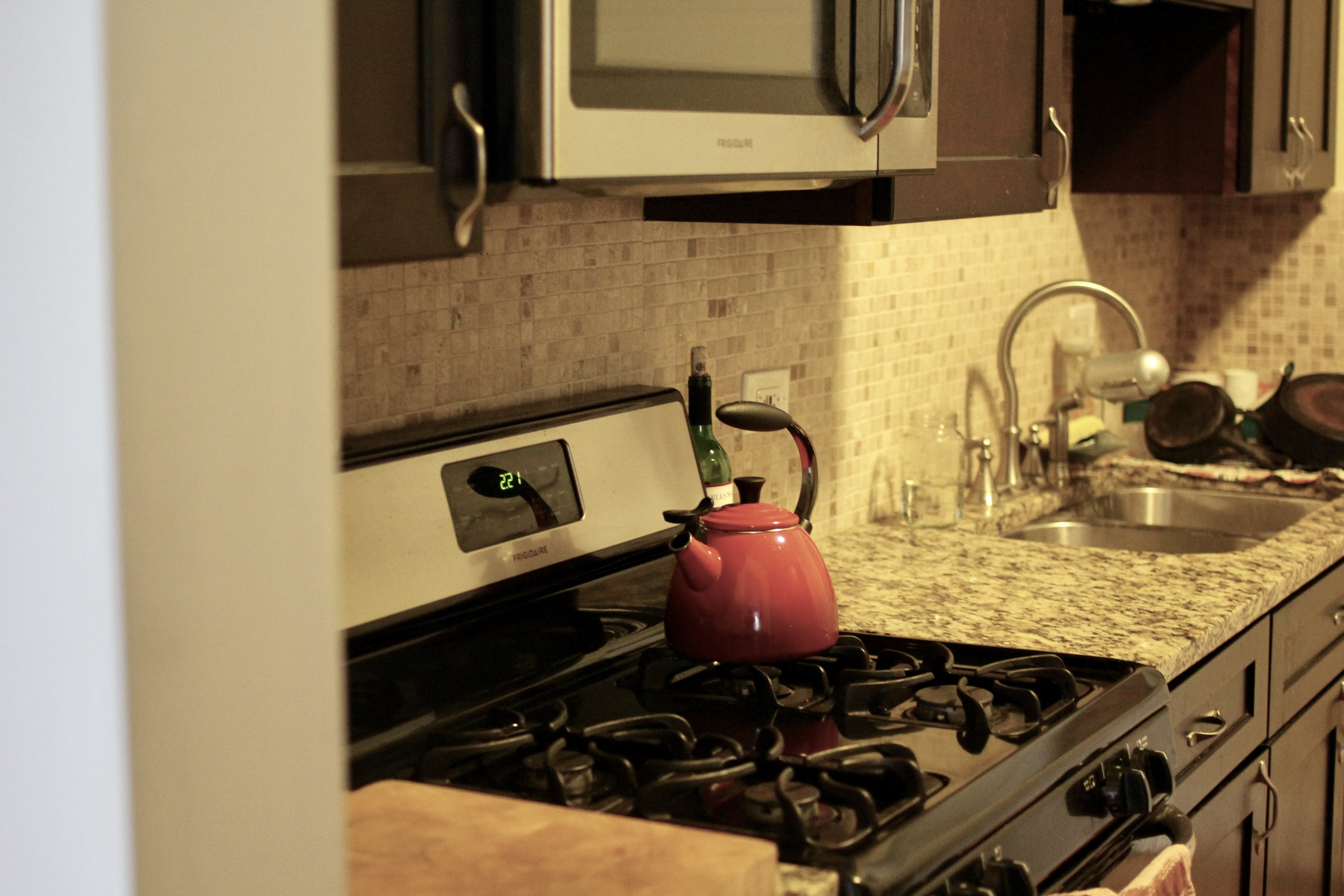 Stovetop in Kitchen with red tea kettle