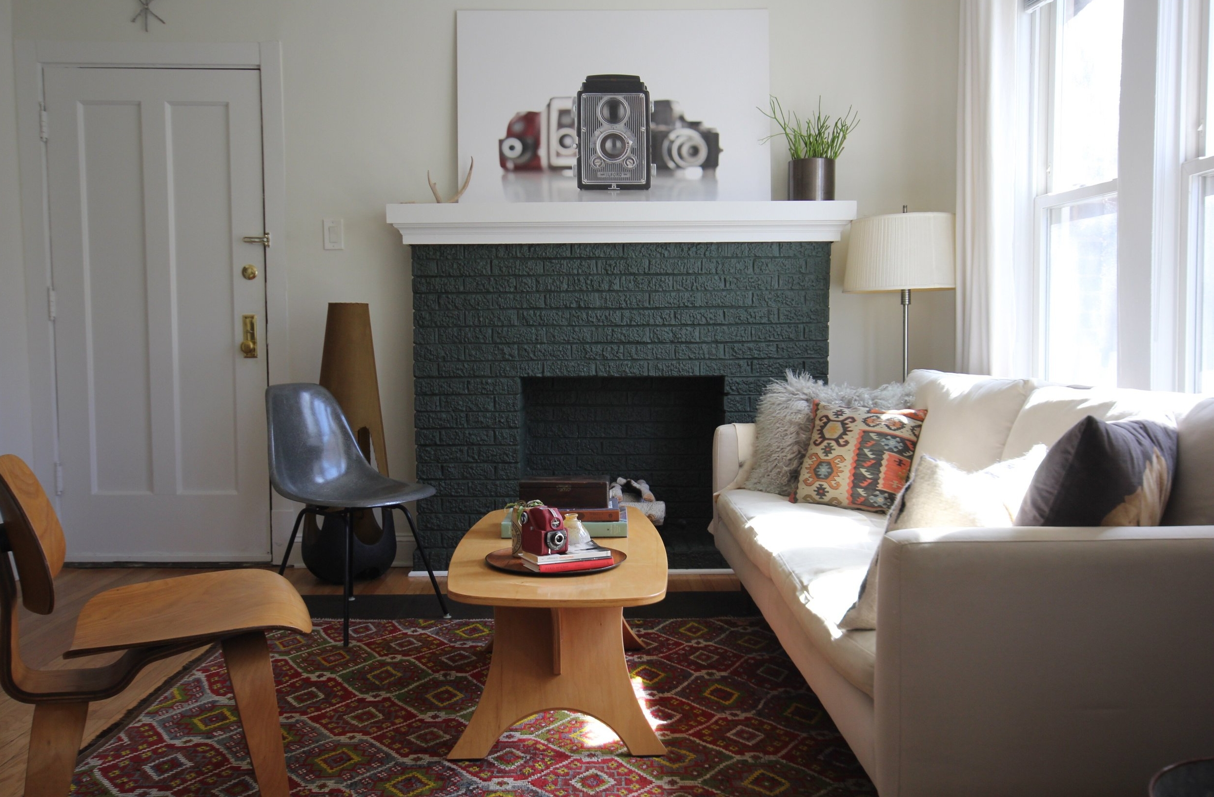 Photo of green, painted brick fireplace in an eclectic living room